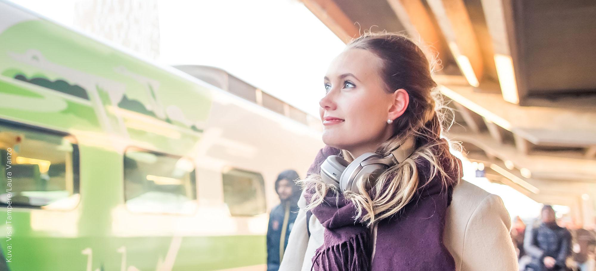 Nuori nainen odottaa junan tuloa asemalla.