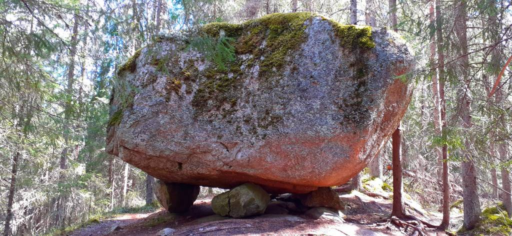 Metsässä on iso siirtolohkare kallion päällä. Sammaleinen iso kivi lepää pienempien kivien päällä, mutta pysyy kuitenkin paikallaan,